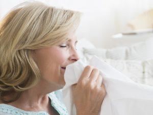 femeie care miroase o haina a partenerului pentru a face fata la stres